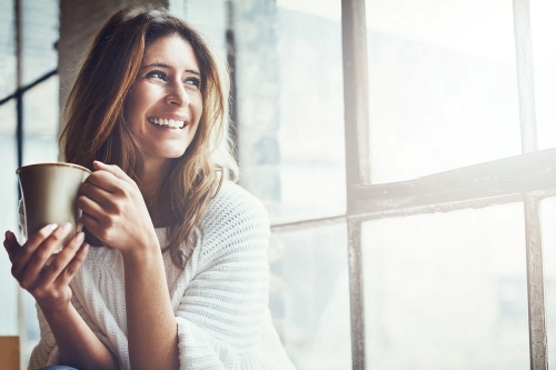 smiling woman sitting at window